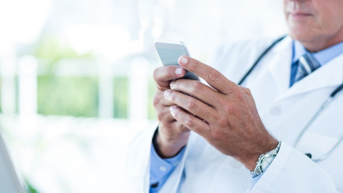 Doctor-using-mobile-phone-to-text