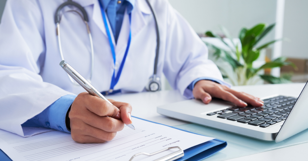 Physician sitting at desk on laptop writing information in document.