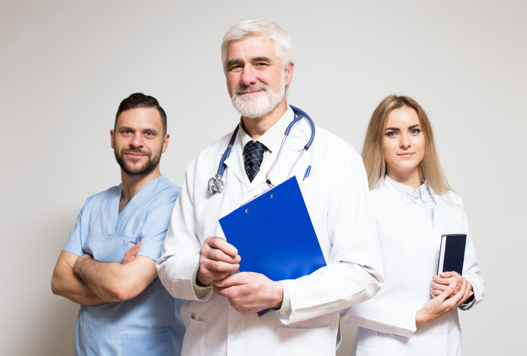 Physicians standing next to each other smiling.