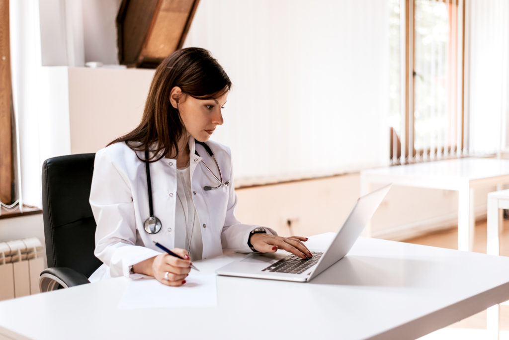 Physician on laptop and writing notes talking to sales rep