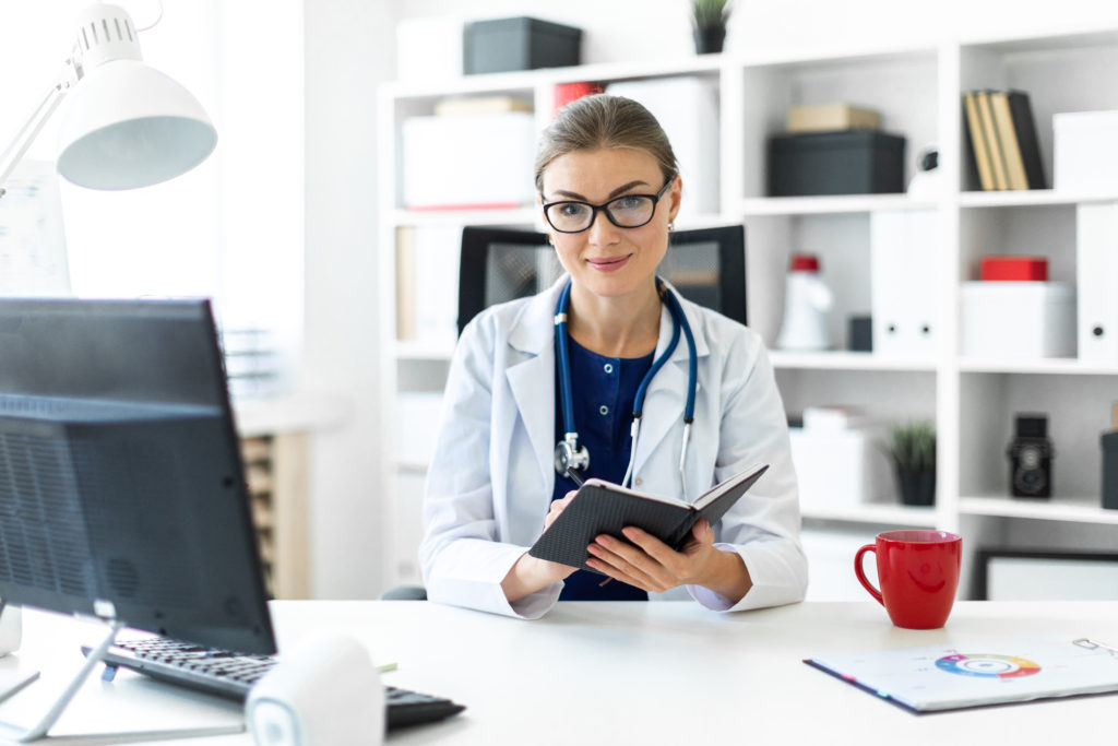 Physician at her desk holding an iPad.